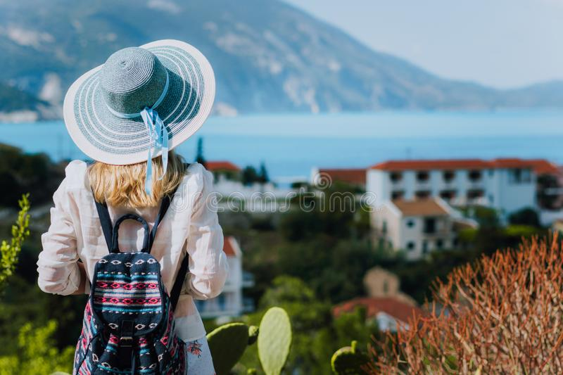 Vintage photo of tourist female with blue sun hat and travel backpack enjoying panorama of colorful small Assos village royalty free stock photos