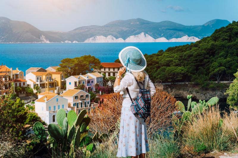 Vintage photo of tourist female wearing blue sun hat and travel backpack enjoying greek coastline in small Assos town royalty free stock images
