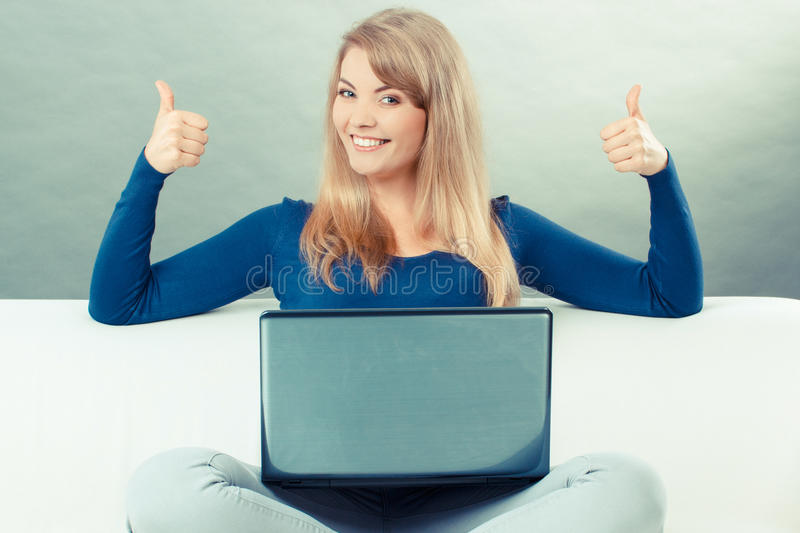 Vintage photo, Woman with laptop sitting on sofa and showing thumbs up. Vintage photo, Happy smiling woman using laptop sitting on sofa and showing thumbs up stock photography