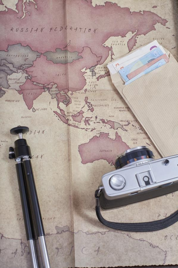 Vintage photographic camera next to a map, a tripod and an envelope of money in euros preparing a trip stock image