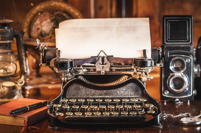 Vintage photography still life with typewriter. Vintage photography still life with typewriter, folding camera, globe map and book on a wood table royalty free stock photos