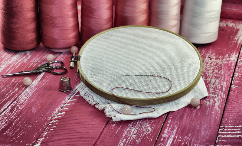 Vintage photos of items for sewing. On a wooden pink background stock photography