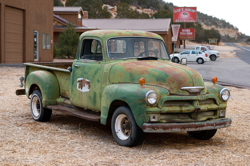 Vintage Pick-Up Truck. A close-up on an old rusty Chevrolet covered with chipped green paint displayed by a roadside retail store in Utah countryside. The file stock photo