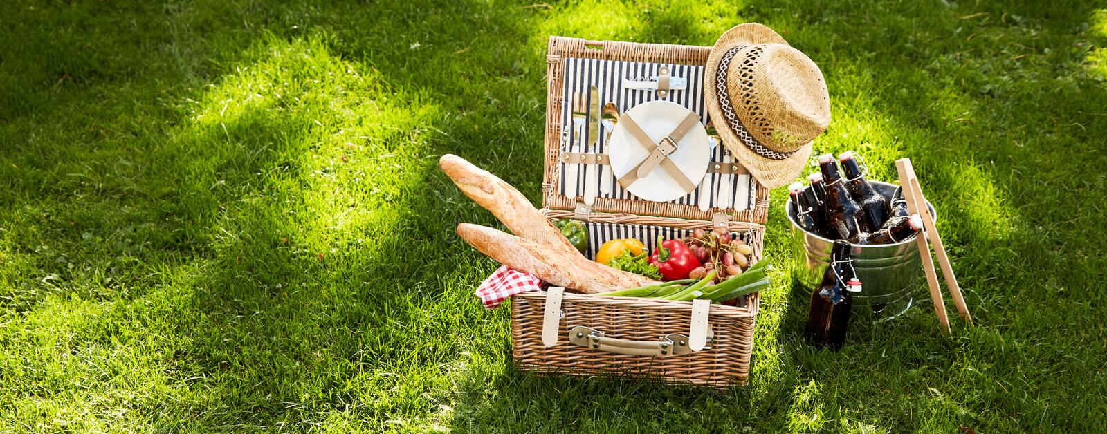 Vintage picnic hamper with vegetarian food. And French baguettes adorned with an old straw hat alongside a silver cooler with bottle of beer on green grass stock photography