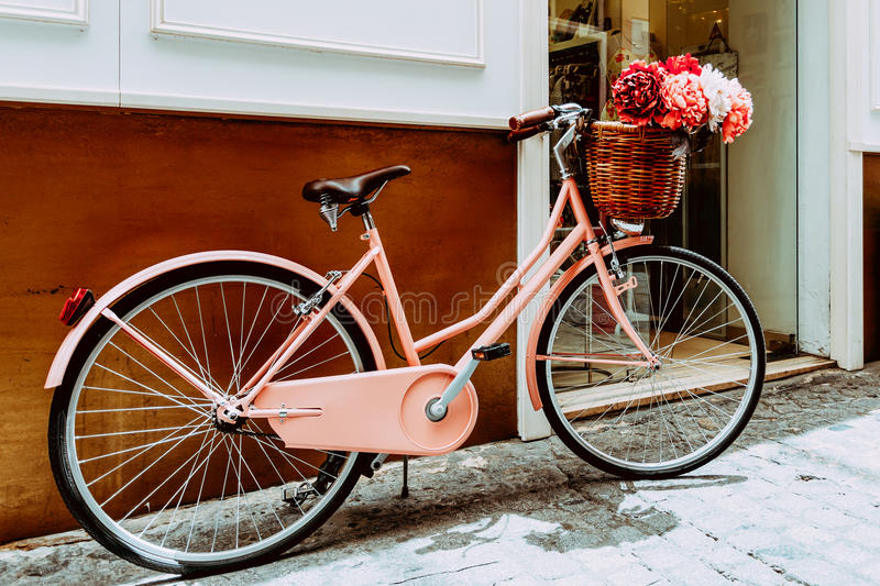 Vintage Pink Bicycle With A Decorative Basket Of Flowers Parking stock photography