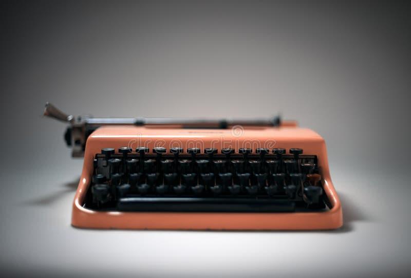 Vintage pink typewriter in evocative spotlight stock image