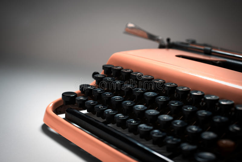 Vintage pink typewriter in evocative spotlight royalty free stock image