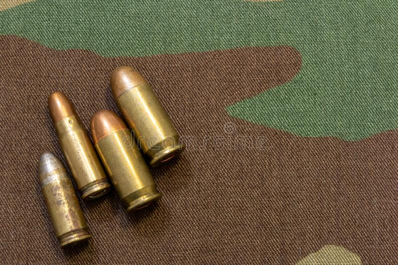Vintage pistol bullets on military camouflage seamless pattern background. War concept stock image