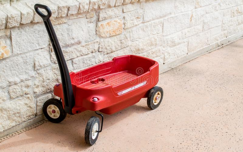 Red Radio Flyer wagon against a stone wall stock photography
