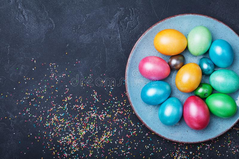 Vintage plate with colorful eggs on black table top view. Easter background. Vintage plate with colorful eggs on black table from above. Easter background royalty free stock photos