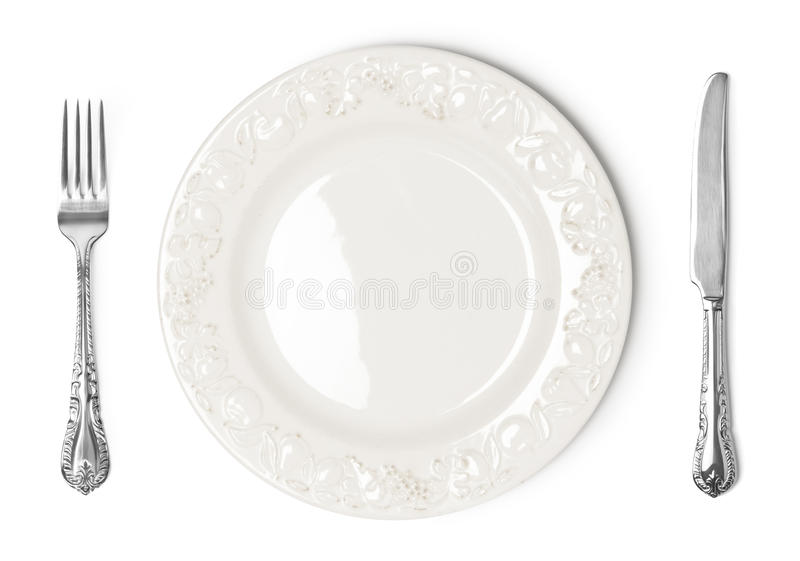 Vintage plate, knife and fork on white background stock photography