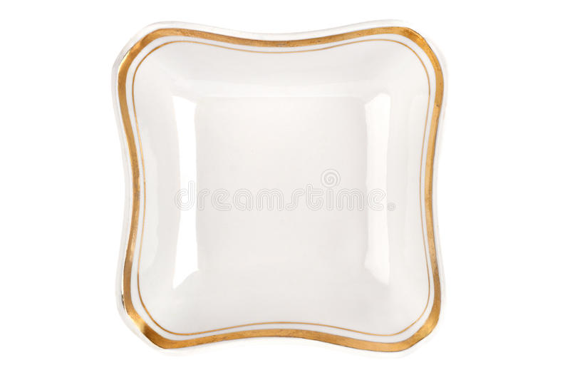 Vintage plate of unusual shape with gold rim isolated. Bowl top view. royalty free stock image