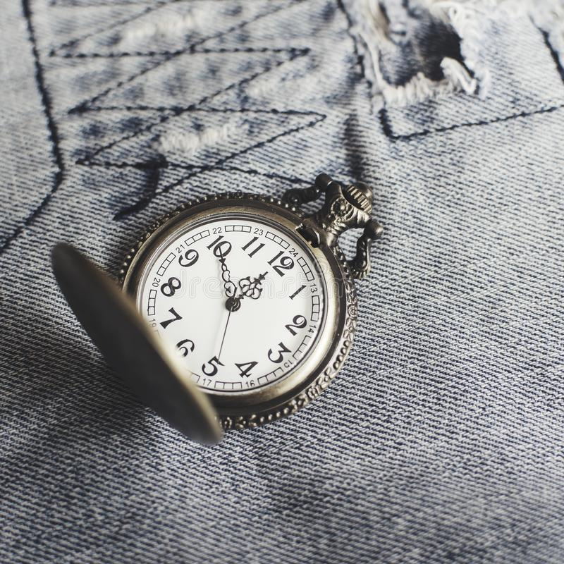 Vintage pocket watch on blue jeans. Close up royalty free stock image