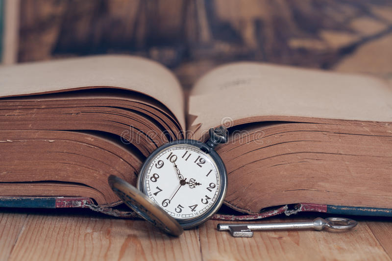 Vintage pocket watch on books. stock images