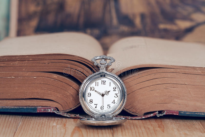 Vintage pocket watch on books. stock photo