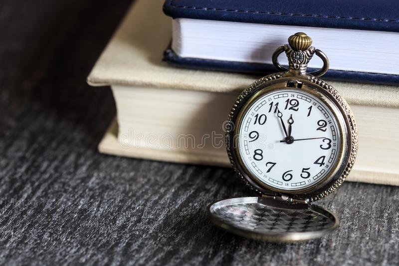 Vintage pocket watch with books royalty free stock photos