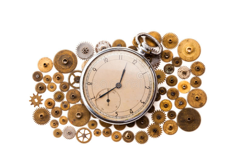 Vintage pocket watch and cogs gears wheels on white background. Vintage clockwork parts closeup. shallow depth of field. Vintage pocket watch and cogs gears royalty free stock photos