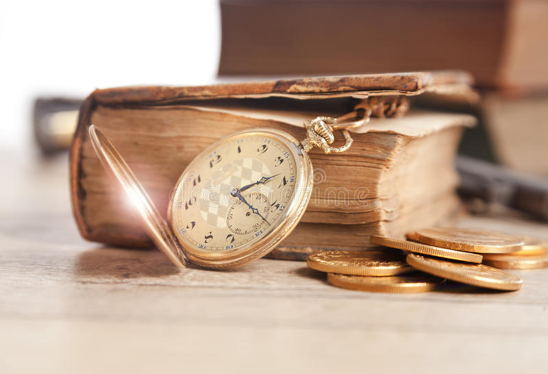 Vintage pocket watch and gold coins. And old book stock image