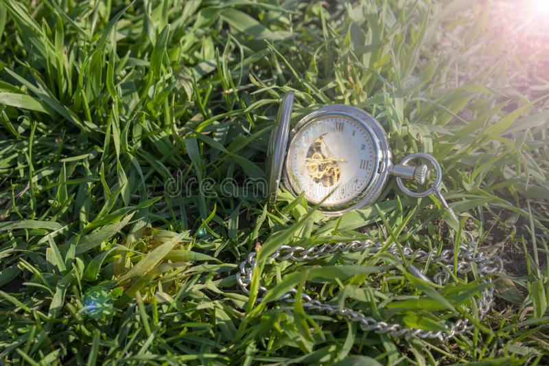 Vintage pocket watch in male hand on a background of green grass. Steampunk watch. Sunny summer day. The clock mechanism is royalty free stock image