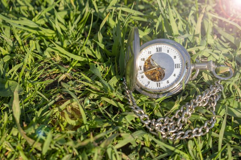 Vintage pocket watch lying on the green grass. Steampunk watch. Sunny summer day. The clock mechanism is partially visible stock photos