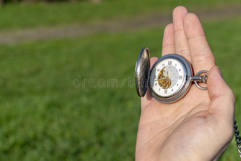 Vintage pocket watch in male hand on a background of green grass. Steampunk watch. Sunny summer day. The clock mechanism is royalty free stock photos