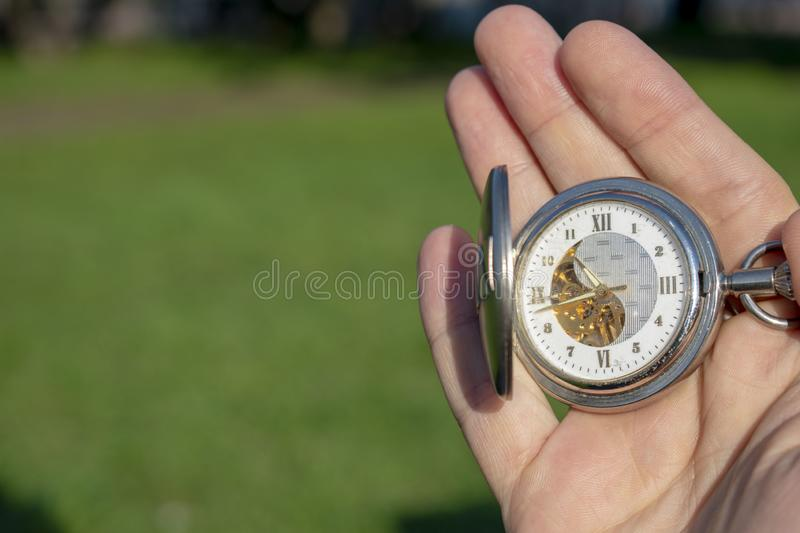 Vintage pocket watch in male hand on a background of green grass. Steampunk watch. Sunny summer day. stock photo
