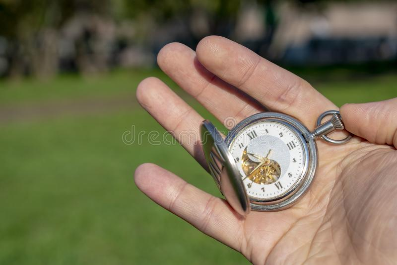 Vintage pocket watch in male hand on a background of green grass. Steampunk watch. Sunny summer day. stock images
