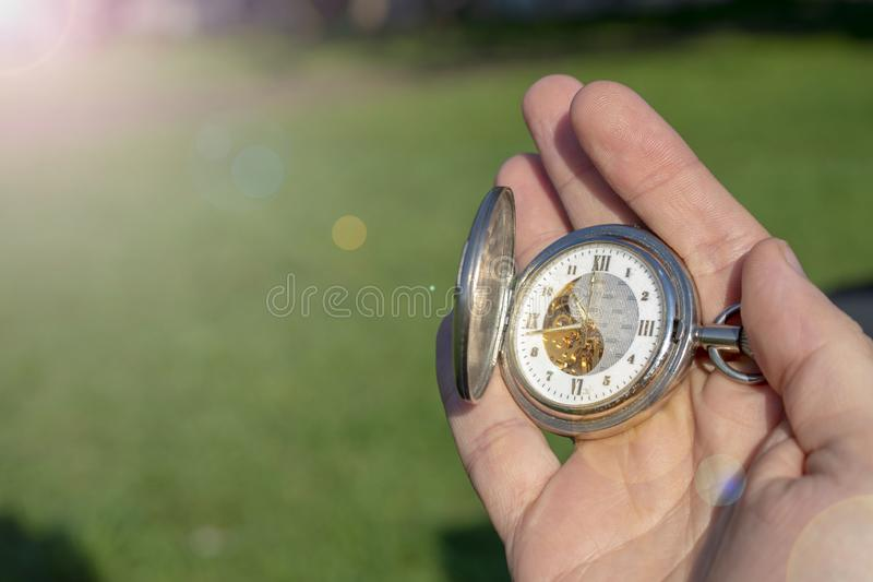 Vintage pocket watch in male hand on a background of green grass. Steampunk watch. Sunny summer day. The clock mechanism is stock photos