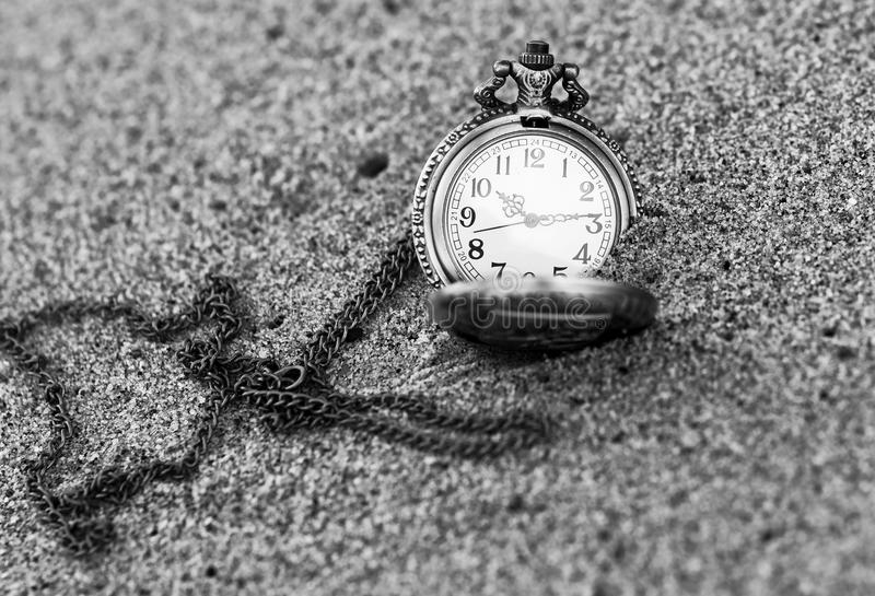 Vintage pocket watch is on the sand. Old metal watch with chain is on the sandy beach royalty free stock image