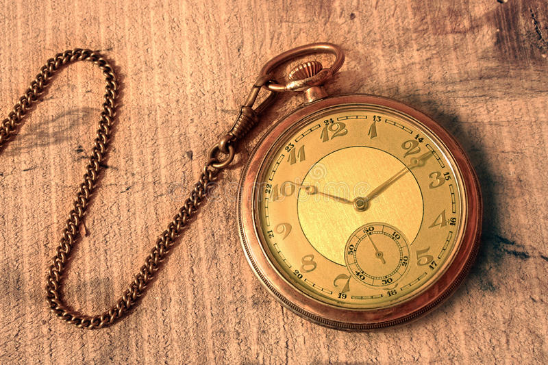 Pocket watch. Vintage pocket watch with wood background stock images