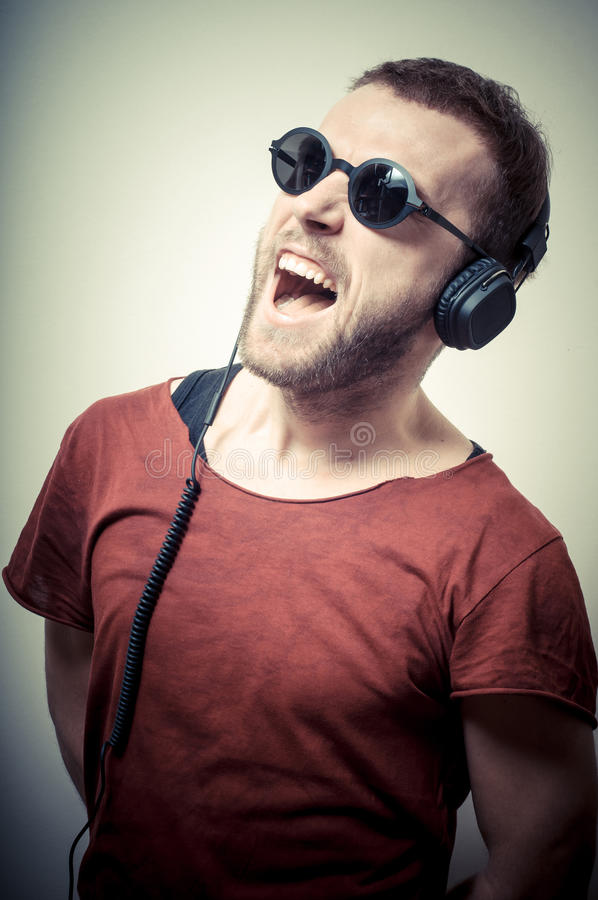 Vintage portrait of fashion guy with headphones and sunglasses. On gray background stock photos