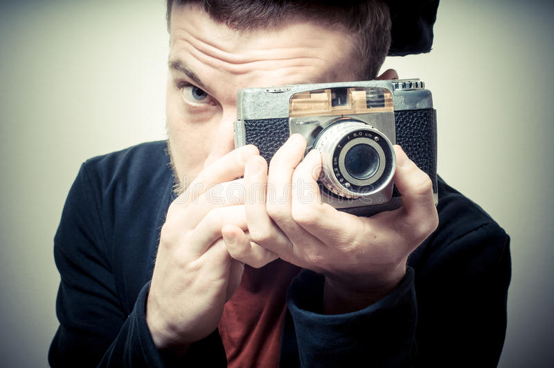 Vintage portrait of fashion guy with old camera. On gray background stock photography
