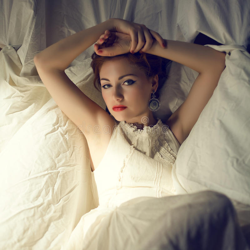 Vintage portrait of glamorous ginger queen-like young woman stock image