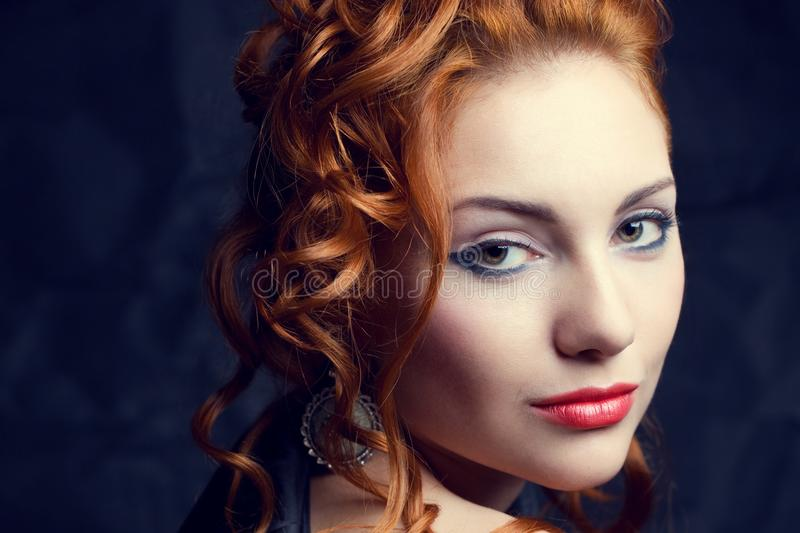 Vintage portrait of glamourous queen like red-haired woman. Vintage portrait of a glamourous queen like red-haired ginger girl posing over wrinkled black paper royalty free stock photo