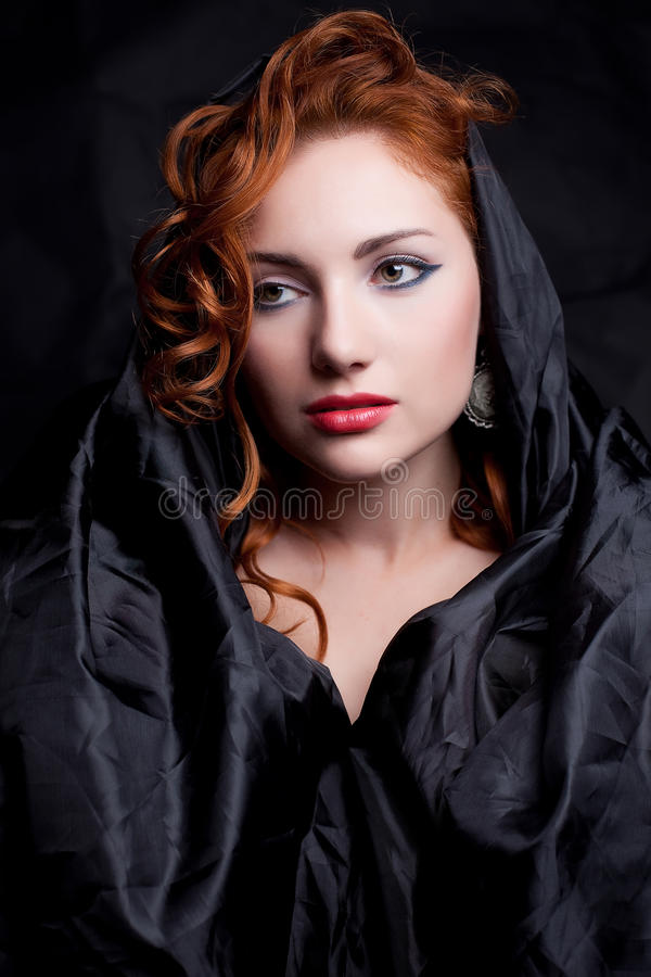 Vintage portrait of glamourous red-haired queen like girl. Vintage portrait of a glamourous red-haired queen like girl over wrinkled black paper background royalty free stock images
