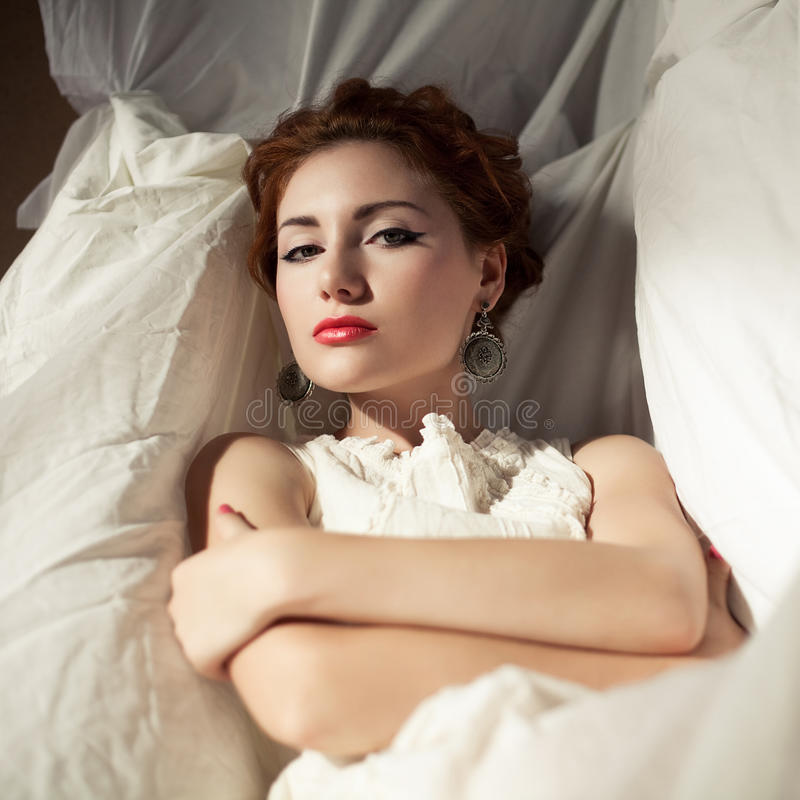 Vintage portrait of red-haired girl in white. Vintage portrait of a beautiful queen like girl in bedroom. Retro style. Daylight. Studio shot royalty free stock photography
