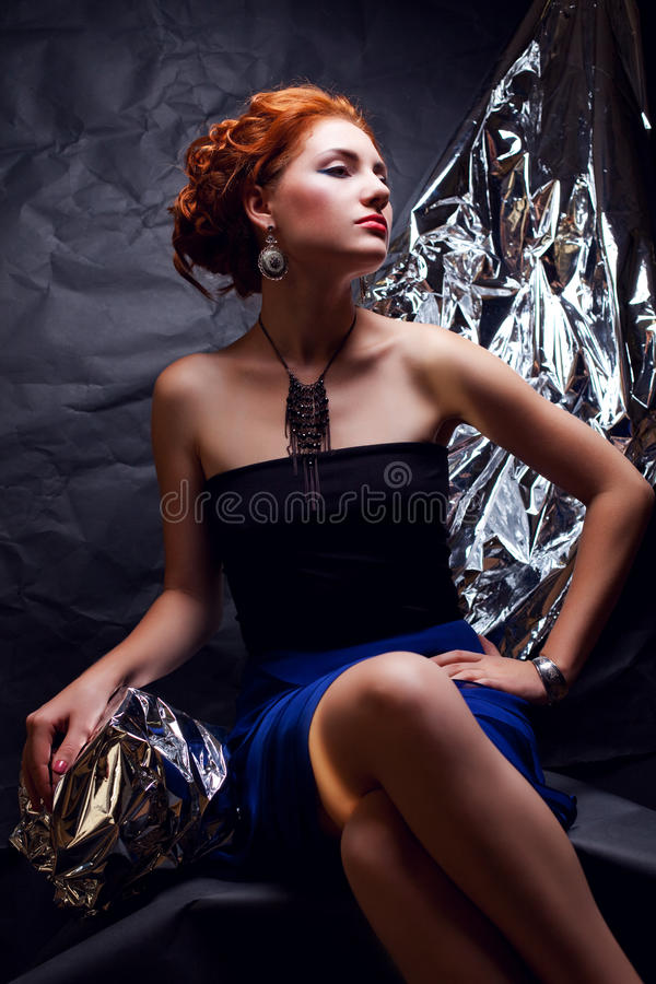 Vintage portrait of seductive ginger model with silver foil royalty free stock photo