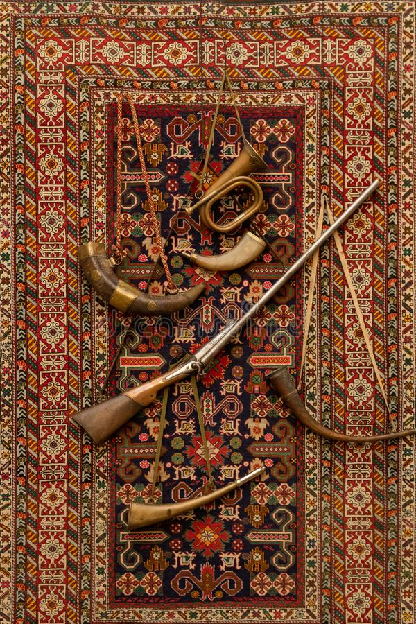 Vintage professional hunting equipment for hunting on the background of the carpet on the wall stock image