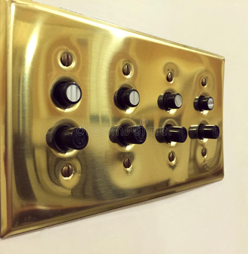 Vintage Push button multiple light switches. Push button vintage light switch in gold toned brass stock photography