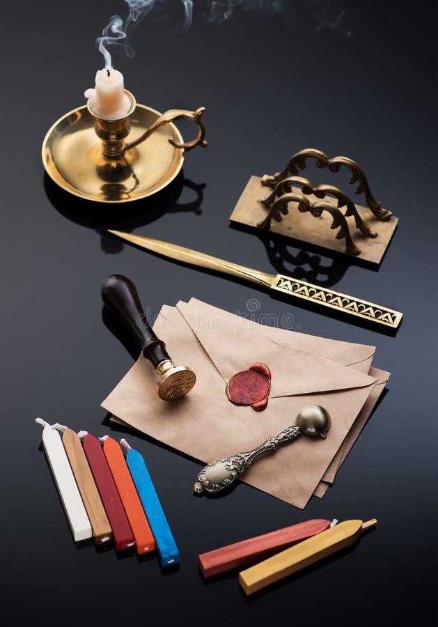 Vintage que escreve o grupo retro: tinteiro de bronze, abridor de letra, envelopes velhos com selo da cera e cera de selagem foto de stock