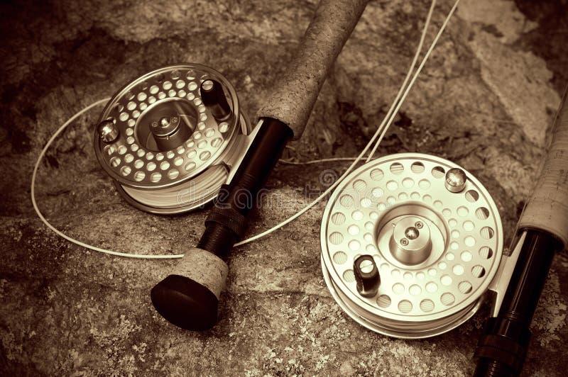 Vintage que olha a pesca com mosca dobro Ros do Sepia em rochas fotos de stock royalty free