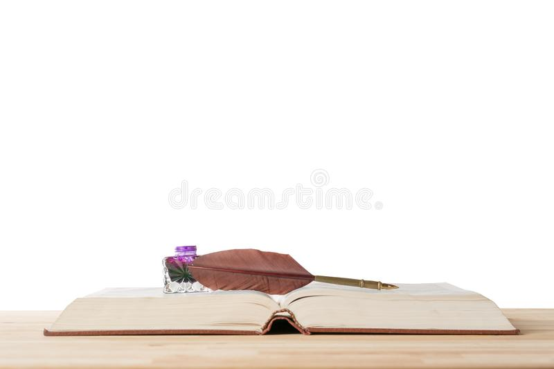 Vintage quill feather pen and inkwell on old opened book against isolated white baxckground. History, writing and literature royalty free stock photos