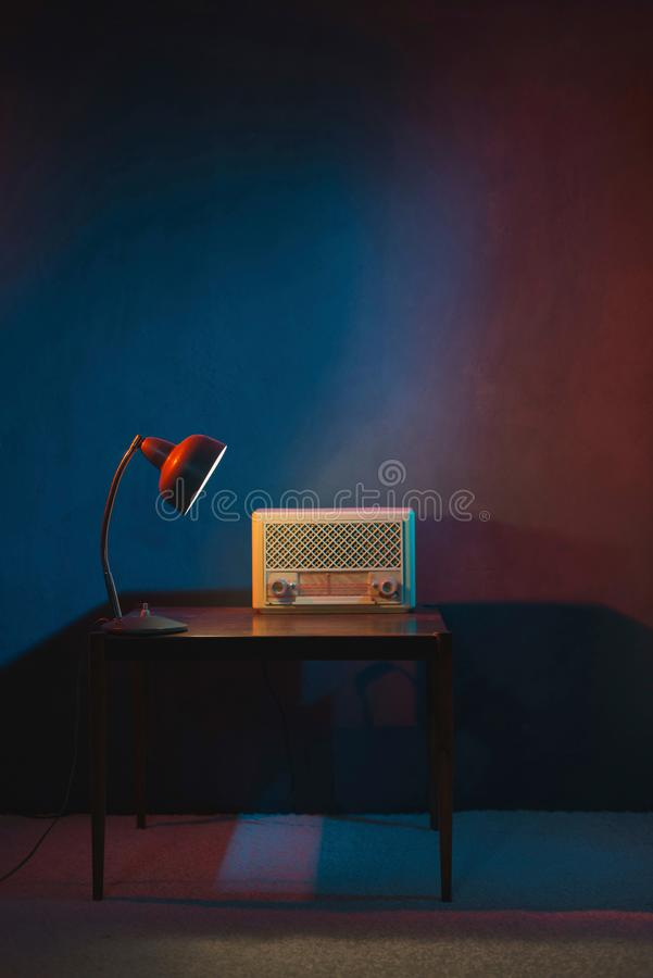 Vintage radio in evening interior lit by desk lamp. royalty free stock photos