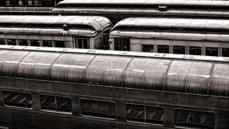Vintage Rail Passenger Cars in Old Train Station. Vintage rail passenger transportation cars lined up in an old railroad train station with vintage finish royalty free stock image