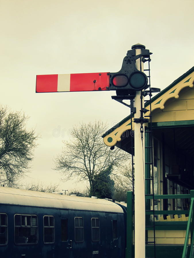 Vintage railway stop signal with signal box and train in the background stock photography