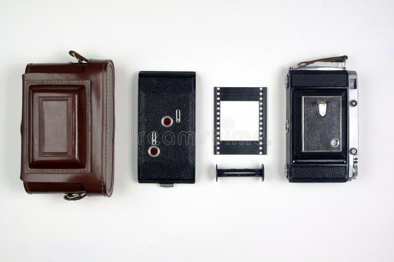 Vintage Rangefinder Film Camera Components Organized on a White Background. Vintage medium format folding film camera components arranged on a white background stock images