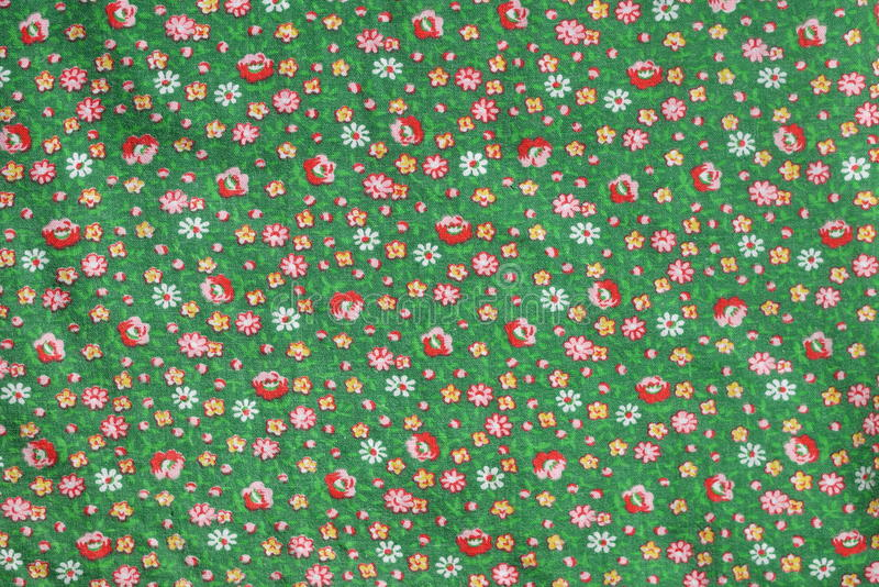 Vintage real fabric 1960s cotton emerald green with red roses and yellow flower pattern. Material close up, repeat pattern for clothes stock image