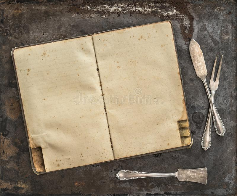 Vintage recipe book Antique silverware rustic background. Vintage recipe book. Antique silverware on rustic metal background royalty free stock photography