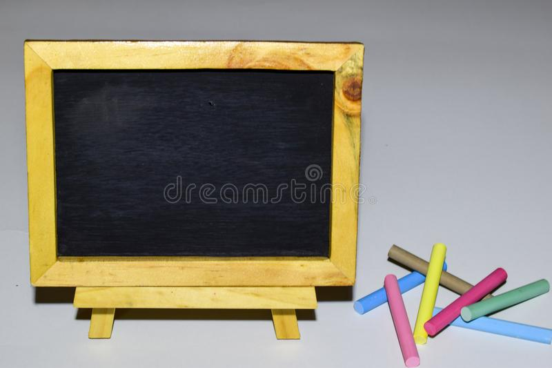 Vintage rectangular chalkboard with colorful chalk isolated on white background stock images