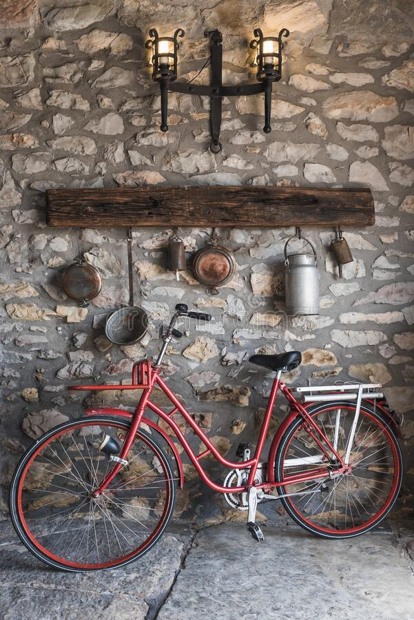 Free Vintage Red Bicycle And Old Kitchen Utensils Hanging On The Wall Royalty Free Stock Photography - 189778327